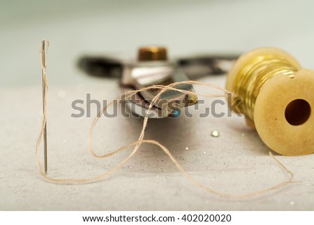 Sewing textile or cloth. Work table of a tailor. Textile tools. Scissors reel of thread, measuring tapes and natural fabric. - stock photo