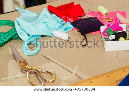 Sewing textile or cloth. Work table of a tailor. Textile tools. Scissors reel of thread,  measuring tapes and natural fabric. Copy space. Top view. - stock photo