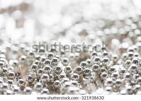 sewing, texture, background, christmas and holiday decoration concept - close up of silver beads on sparkling sequined textile texture - stock photo