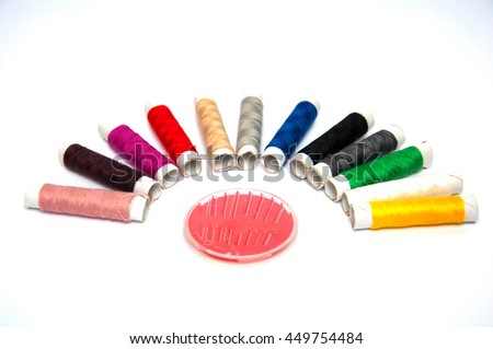 Sewing thread and needles isolated on white background - stock photo