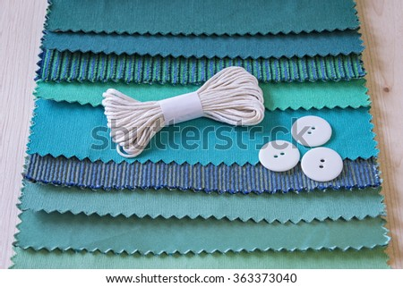 Sewing thread lies on different fabric patterns in a studio for interior, with three buttons. - stock photo
