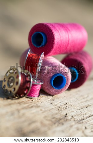 Sewing thread on the balance beam with a blurred background - stock photo