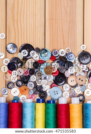 sewing threads and buttons on wooden table