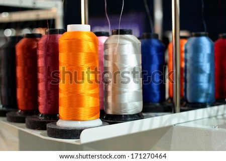 Sewing threads multicolored on spool - stock photo