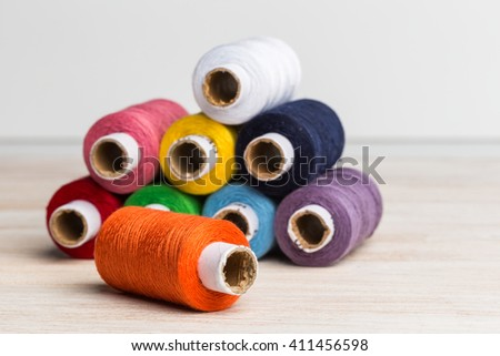 Sewing threads of different colors stacked pyramid on a wooden surface. - stock photo
