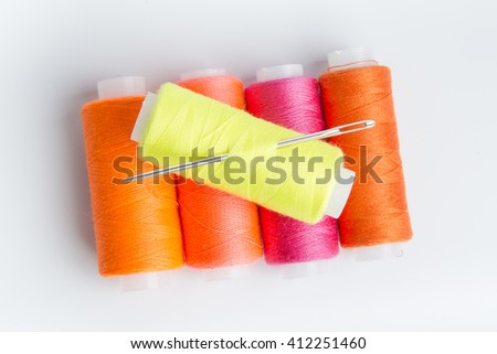 Sewing threads of different colors stacked pyramid on white background - stock photo