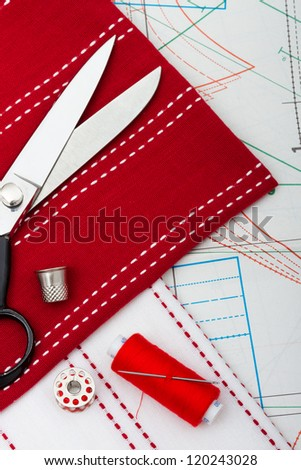 sewing tools and fabric against sheet of professional clothing patterns - stock photo