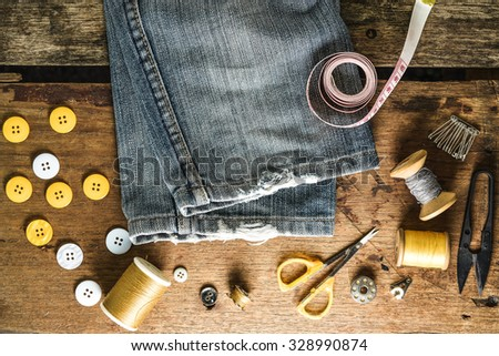Sewing tools and sewing kit on grunge wood background - stock photo