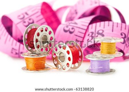 Sewing tools: bobbins with threads and measuring tape isolated on white - stock photo