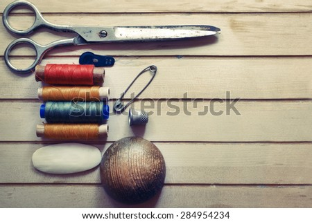 Sewing tools on wooden surface. Tailor's work table. textile or fine cloth making. - stock photo