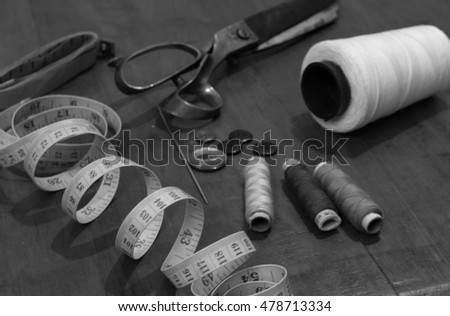 Sewing tools with old scissor on wooden background.