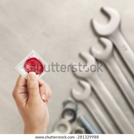 sex at work, holding condom in a hand, spanners on the metal table background - stock photo