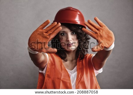 Sex equality and feminism. Sexy girl construction worker builder in orange vest and hard hat showing stop sign hand gesture. - stock photo