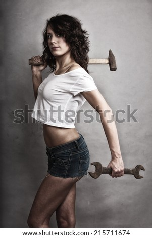 Sex equality and feminism. Sexy girl holding hammer and wrench spanner tools. Attractive woman working as repairman. - stock photo