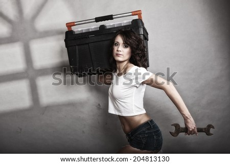 Sex equality and feminism. Sexy girl holding toolbox and wrench spanner tool. Attractive woman working as repairman or mechanic - stock photo