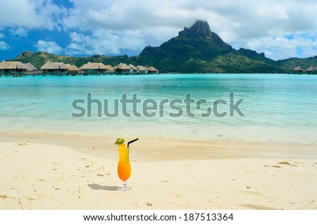 Sex on the beach cocktail on the beach of a luxury vacation resort in the lagoon with a view on the tropical island of Bora Bora, near Tahiti, in French Polynesia. - stock photo