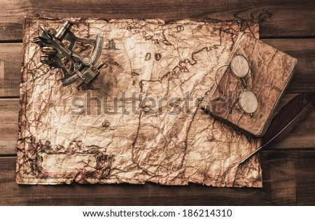 Sextant and logbook on a vintage map  - stock photo