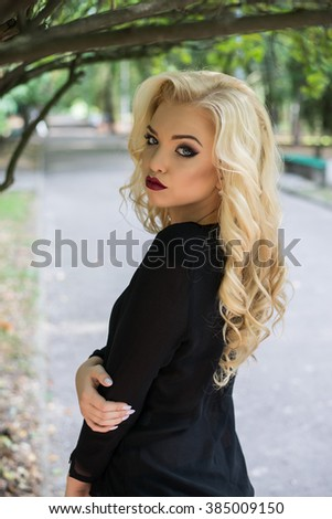 Sexual beautiful blonde girl in a black dress posing in the park. Perfect skin.