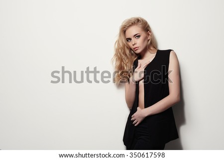 sexual beautiful girl is in fashion style.young blond woman on the wall - stock photo
