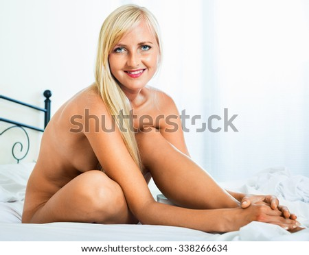 Sexual blonde smiling girl posing in bedroom naked