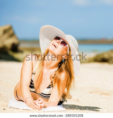 Sexual brunette girl take sunbath on the beach, happy female in  swimwear in sunglasses and white hat enjoying summer holidays leying on white sand. Holidays, vacation, lifestyle concept. Squared - stock photo