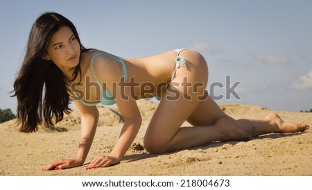 Sexual girl in a bikini relaxing on a sandy beach