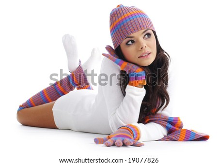 sexual girl in a multicolor winter  hat and gloves lays on white to a floor. Winter fashion. - stock photo