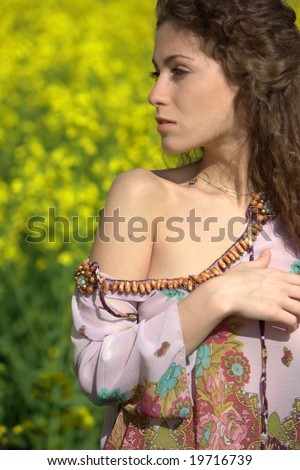 Sexual girl with curly hair in a field with yellow flowers
