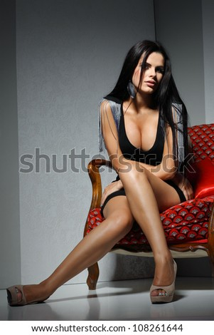 Sexual  girl with dark hairs, sitting on a red arm-chair - stock photo