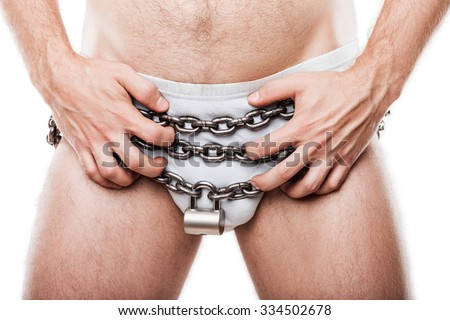 Sexual issues and forbidden sex concept - naked man hand holding padlock locked metal chain chastity belt over pants underwear