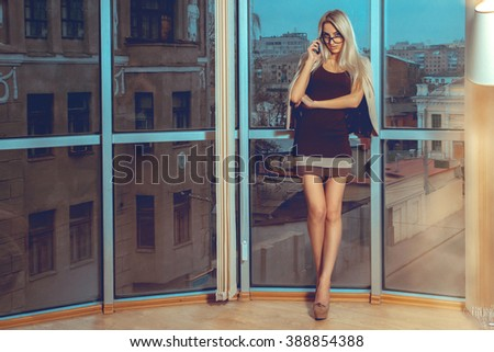 Sexual lady talking phone by the window with city views. Business woman talking phone. City views behind the window in the office. Business concept. - stock photo