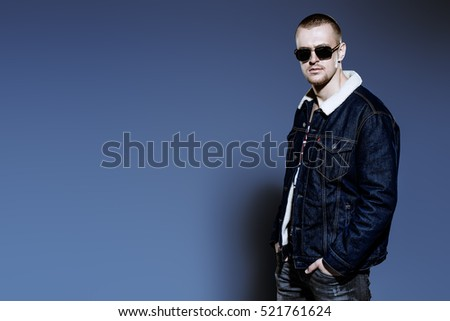 Sexual male model posing in jeans clothes and sunglasses. Short hair styling. Studio fashion shot.