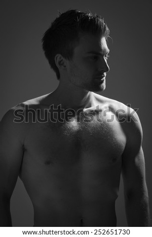 Sexual muscular man posing over dark background. Low key - stock photo