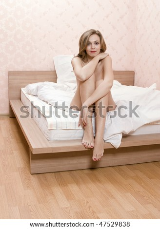 sexual naked girl sitting on bed waiting for sex with lover - stock photo