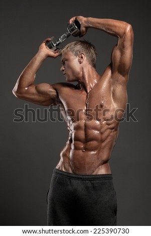 Sexual portrait of very muscular man's model without shirt on a gray background in studio - stock photo