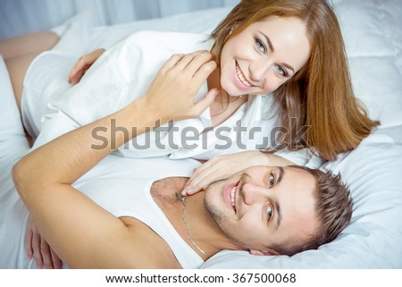 Sexual scene of gentle and affectionate young couple in the bedroom - stock photo