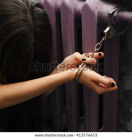 Sexual slavery. Young woman locked with handcuffs