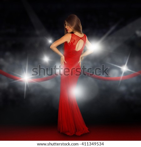 Sexual young lady on red carpet is posing in paparazzi flashes - stock photo