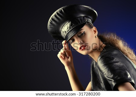Sexual young woman alluring in fitting leather suit and a cap of police officer. Beauty, fashion. - stock photo