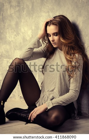 Sexual young woman with beautiful long hair sitting on a floor. Beauty, fashion. Cosmetics, dark make-up. Hairstyle.