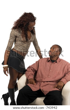 Sexy African American woman in a casual denim skirt and snake skin print top sitting in a white chair with a glass of wine