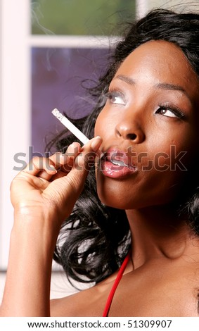 Sexy African American young woman smoking cigarette - stock photo
