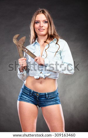 Sexy alluring seductive woman holding monkey wrench gas grips. Strong girl feminist working in man profession. Gender social issue. - stock photo