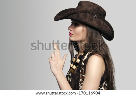 Sexy american cowgirl with cowboy hat blowing her fingers in a gun shape - stock photo