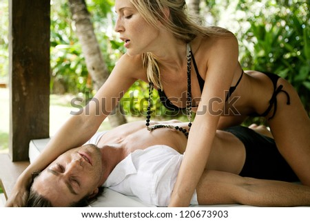 Sexy and attractive couple being passionate while lounging on a tropical garden bed while on vacations in an exotic lush destination, outdoors.