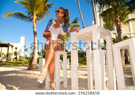 Sexy and attractive girl on luxury tropical garden, in caribbean hotel. Happy brunette woman on travel holidays vacation outdoors.
