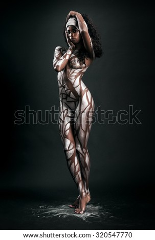 Sexy and beautiful african model body covered with painted polygons - stock photo