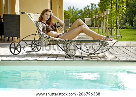 Sexy and beautiful young brunette woman relaxing on deck chair - stock photo