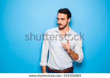sexy and confident handsome man on a blue background, pointing - stock photo