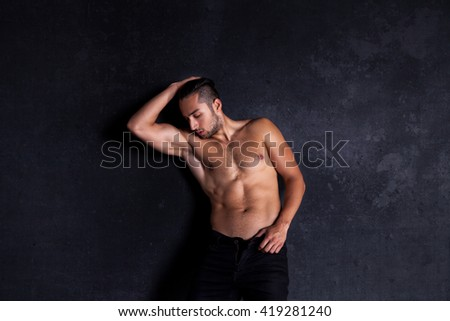 Sexy and expressive shirtless male model flirting against black background